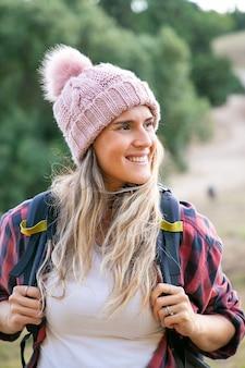 帽子とバックパックを運ぶ幸せな美しい女性の肖像画。自然の上に立っている白人の笑顔の女性旅行者。バックパッキング観光、冒険、夏休みのコンセプト