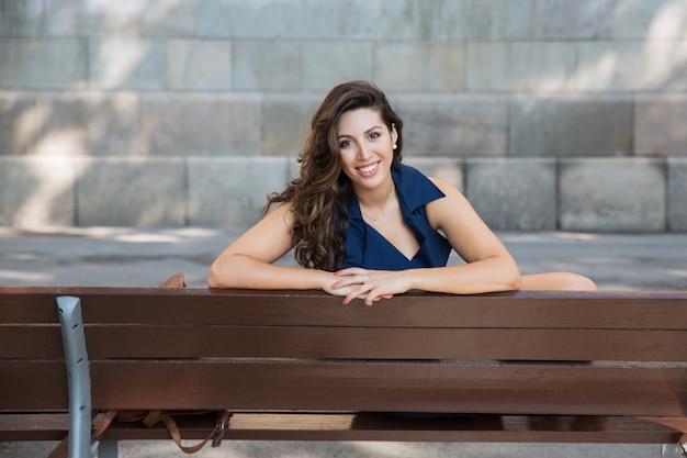 Портрет счастливый красивая женщина, сидя на скамейке