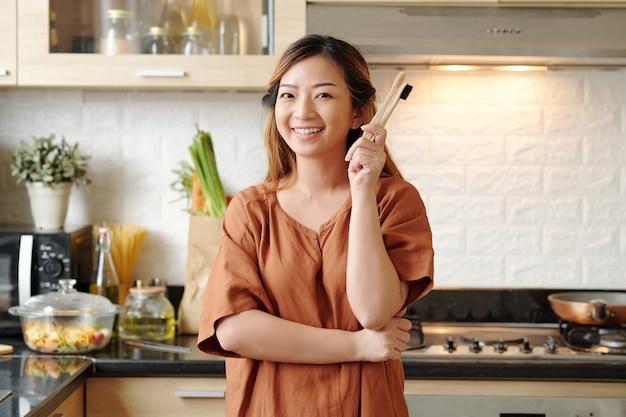 2つの竹の環境に優しい歯ブラシを持っている幸せな美しい若い女性の肖像画