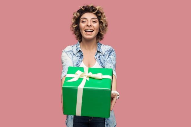 곱슬머리 헤어스타일을 한 파란 셔츠를 입은 행복한 아름다운 젊은 여성의 초상화가 카메라를 바라보며 이빨 미소로 녹색 선물 상자를 줍니다. 스튜디오 촬영, 분홍색 배경, 절연, 실내