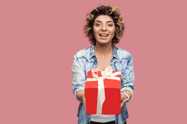 곱슬머리 헤어스타일을 한 파란색 셔츠를 입은 행복한 아름다운 젊은 여성의 초상화가 카메라를 바라보며 이빨 미소로 빨간 선물 상자를 줍니다. 스튜디오 촬영, 분홍색 배경, 절연, 실내