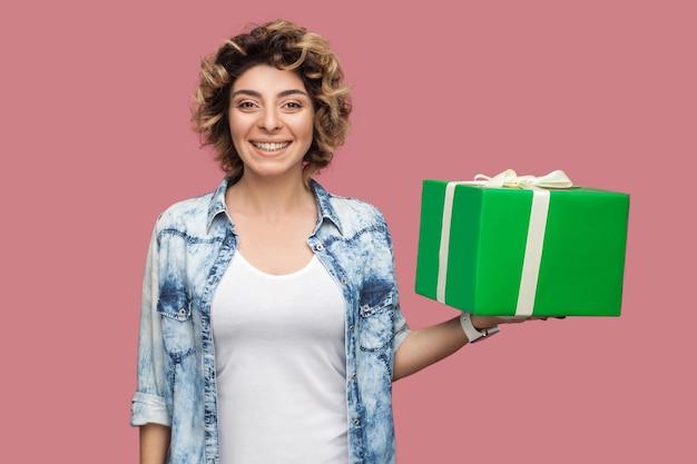 곱슬머리 헤어스타일을 한 파란 셔츠를 입은 행복한 아름다운 젊은 여성의 초상화가 카메라를 바라보며 이빨 미소로 녹색 선물 상자를 들고 있습니다. 스튜디오 촬영, 분홍색 배경, 절연, 실내