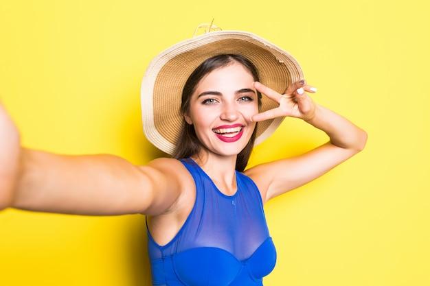 彼女の電話でselfieを取り、笑みを浮かべて、黄色の壁に麦わら帽子で水着を着て幸せな美しい若い女性の肖像画