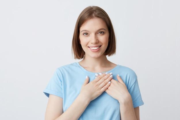 Портрет счастливой красивой молодой женщины в синей футболке держит руки на области сердца