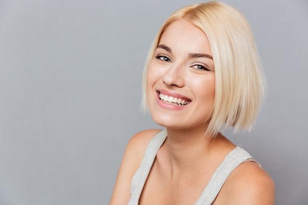 灰色の壁の上のブロンドの髪を持つ幸せな美しい若い女性の肖像画