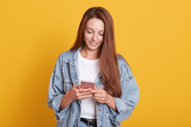 Портрет счастливой красивой молодой женщины с темными прямыми волосами текстовых сообщений на свой телефон и улыбается, проверка социальной сети, носить джинсовую куртку, позирует изолирован на желтом