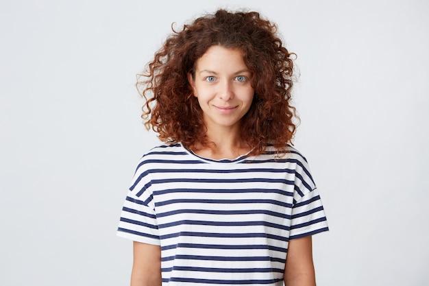 긴 곱슬 머리를 가진 행복 한 아름 다운 젊은 여자의 초상화 스트라이프 티셔츠를 착용
