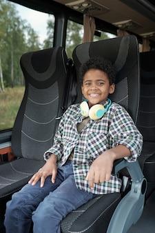 Портрет счастливого темнокожего мальчика с вьющимися волосами, сидящего на сиденье автобуса и едущего в одиночестве на автобусе