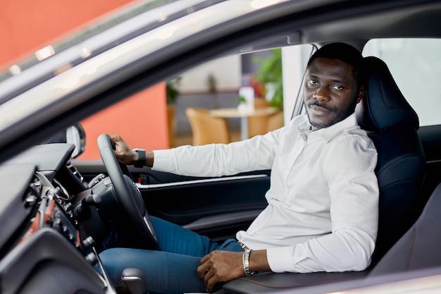 車のショールームで表される高級車の中の幸せな黒人実業家の肖像画。