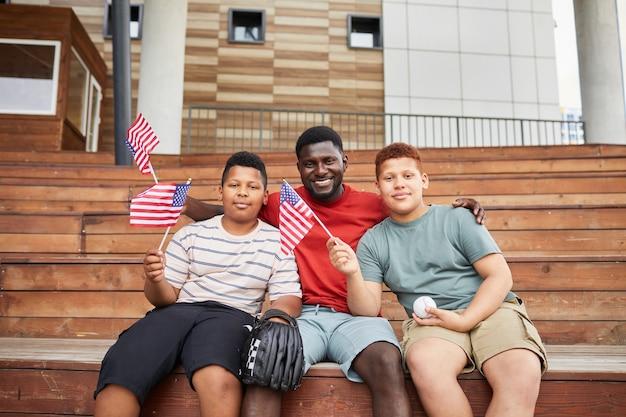 彼らが一緒に野球の試合を訪問している間、アメリカの国旗で10代の息子を抱きしめる幸せな黒人の父の肖像画
