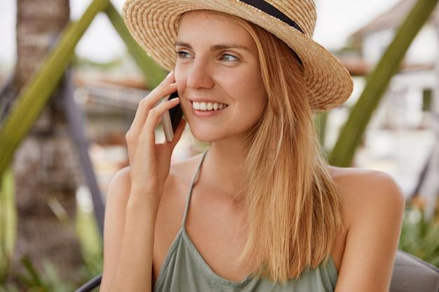 행복한 금발 여성의 초상화는 밀짚 모자를 쓰고 행복한 미소를 지으며 긍정적으로 보이고 휴대 전화를 통해 남자 친구와 즐거운 이야기를 나누며 해변 휴양지에 대한 인상을 공유합니다. 사람과 이야기