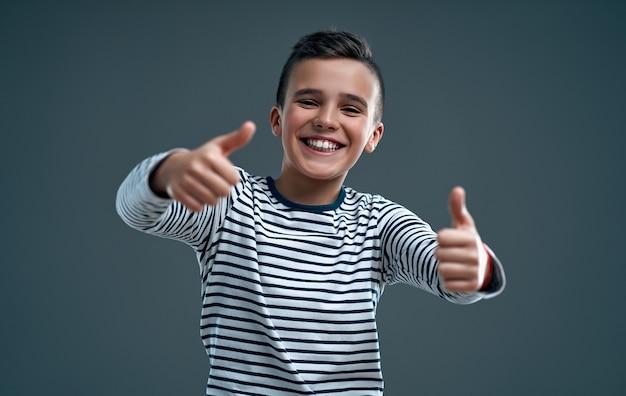 灰色の上に分離された、親指を立てるジェスチャーを示す幸せな少年の肖像画。