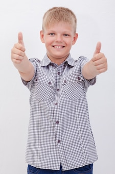 親指のジェスチャーを示す幸せな少年のポートレート