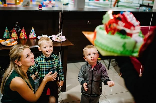 Портрет счастливых мальчиков с матерью, празднующей день рождения, готовятся задуть свечи на торте.