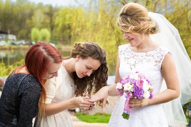 花嫁介添人に結婚指輪を示す幸せな花嫁の肖像画