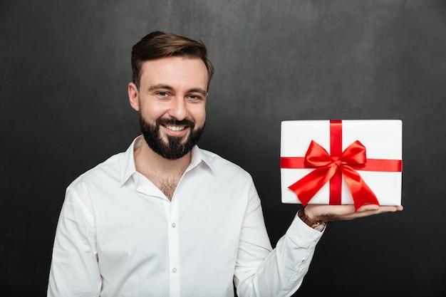 Портрет счастливого человека брюнет демонстрируя белую присутствующую коробку с красным смычком на камере и усмехаясь над темной серой стеной