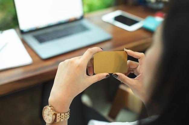ゴールドのクレジットカードを持っている幸せなビジネスウーマンの肖像、クレジットカードは、カード所有者が商品やサービスに基づいて商人に支払うことを可能にするためにユーザーに発行される支払いカードです。