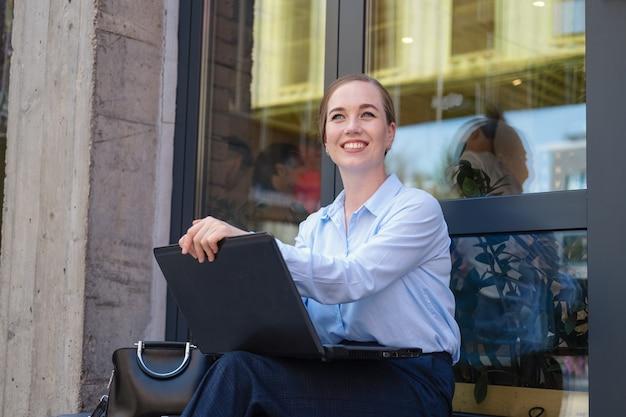 웃으면서 야외에서 일하는 행복한 비즈니스 젊은 여성의 초상화는 노트북에서 프로젝트를 만듭니다. 고품질 사진