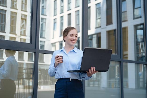 커피를 마시고 야외에서 일하는 동안 웃고 있는 행복한 비즈니스 젊은 여성의 초상화는 커피를 마시는 동안 메모장으로 노트북에서 프로젝트를 만듭니다. 고품질 사진