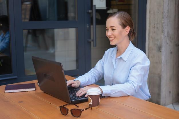 카페에 앉아서 야외에서 일하는 동안 웃고 있는 행복한 비즈니스 젊은 여성의 초상화는 커피를 마시는 동안 메모장으로 노트북에서 프로젝트를 만듭니다. 고품질 사진