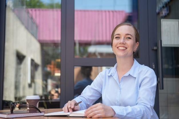 카페에 앉아 야외에서 일하는 행복한 비즈니스 젊은 여성의 초상화는 커피를 마시는 동안 메모장으로 프로젝트를 만듭니다. 고품질 사진