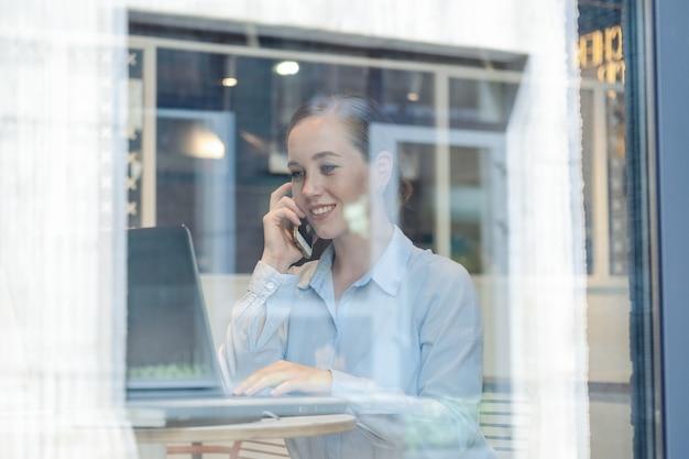 행복한 비즈니스 젊은 여성의 초상화, 전화 통화 및 작업 중에 웃고 있는 동안 창 근처 카페에서 노트북으로 프로젝트를 만드세요. 고품질 사진