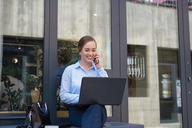 전화 통화를 하고 야외에서 일하는 동안 웃고 있는 행복한 비즈니스 젊은 여성의 초상화는 커피를 마시는 동안 메모장으로 노트북에서 프로젝트를 만듭니다. 고품질 사진 프리미엄 사진