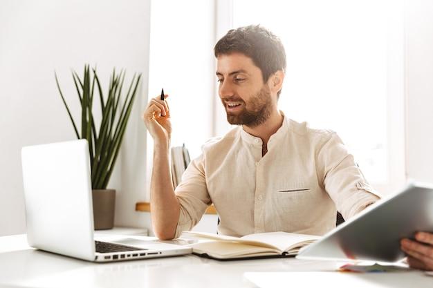 Портрет счастливого делового мужчины 30-х годов в белой рубашке, работающего с ноутбуком и бумажными документами, сидя в ярком офисе