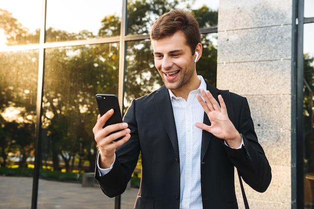 Портрет счастливого бизнесмена в костюме, держащего мобильный телефон, стоя на открытом воздухе против здания