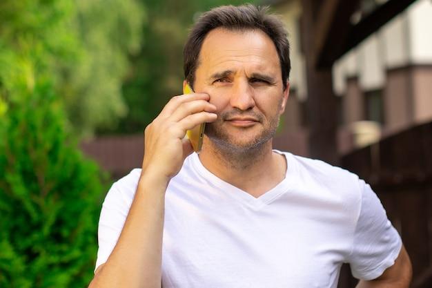 携帯電話で屋外で幸せなビジネスマンの肖像画。中年の自信を持ってハンサムな男は、電話をかけ、携帯電話を話し、スマートフォンを持っています。オンラインコンサルティング、携帯電話事業者のコンセプト、コピースペース