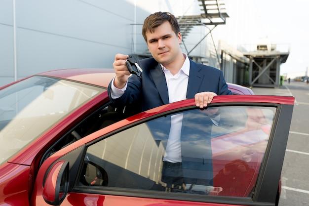 キーと新しい車でポーズをとって幸せな実業家の肖像画