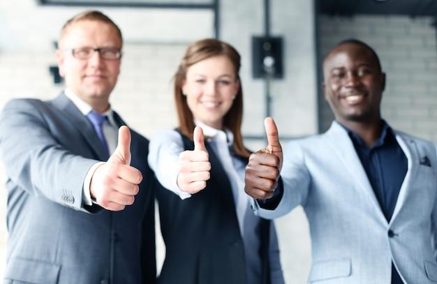 엄지손가락을 보여주는 사무실에 서 있는 행복 한 기업인의 초상화