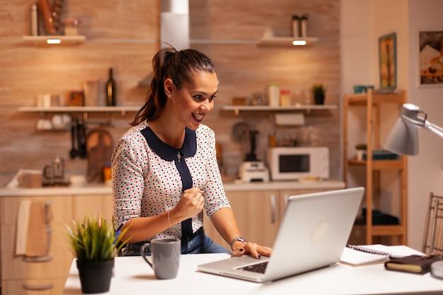 自宅で仕事の締め切りを終えた後、くいしばられた握りこぶしで幸せな実業家の肖像画。深夜に最新のテクノロジーを使用して、仕事、キャリア、ネットワーク、ライフスタイルのために残業している従業員。