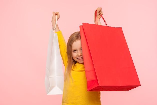 큰 꾸러미를 들고 행복하게 웃고 있는 행복한 평온한 어린 소녀의 초상화, 어린이 가게에서 쇼핑하는 것에 흥분하는 블랙 프라이데이 판매. 분홍색 배경에 고립 된 실내 스튜디오 촬영