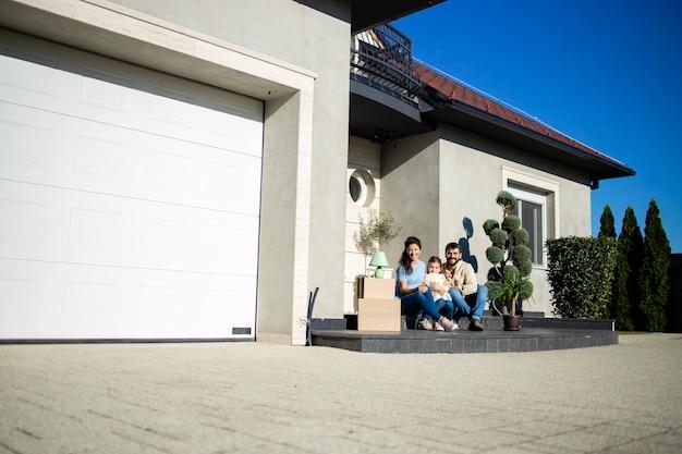 이사할 준비가 된 새 집 현관에 앉아 있는 행복한 백인 가족의 초상화.