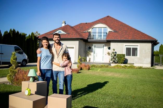 Портрет счастливой кавказской семьи, стоящей перед своим новым домом, готовым к заселению.