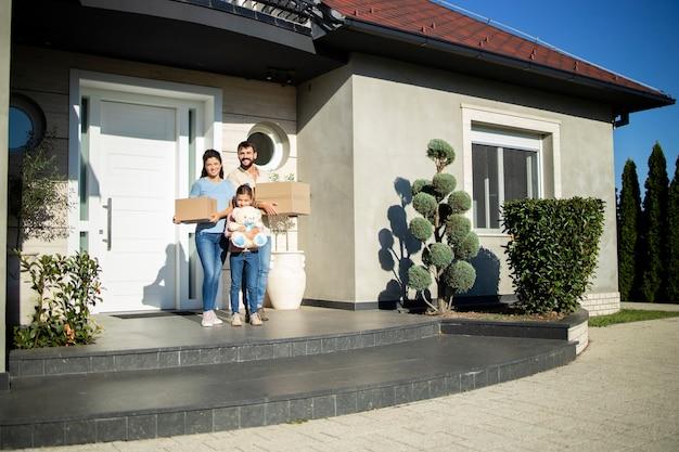Портрет счастливой кавказской семьи, стоящей на крыльце своего нового дома, готового к заселению.