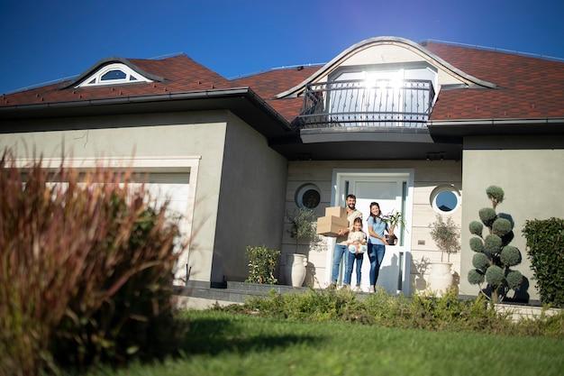 이사할 준비가 된 새 집 현관에 서 있는 행복한 백인 가족의 초상화.
