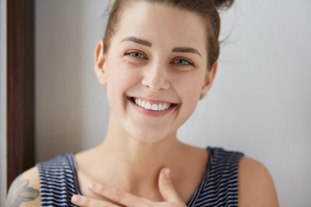 ブルネットの髪のお団子と幸せな白人少女の肖像画、彼女の肩にタトゥー、剥き出しのトップ。魅力的な女性が白い歯を見せて笑って、無限の喜びで胸に手を当てます。