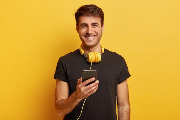 幸せな白人男性の肖像画は、ヘッドフォンの素晴らしい音と品質を楽しんで、現代の携帯電話を保持しています