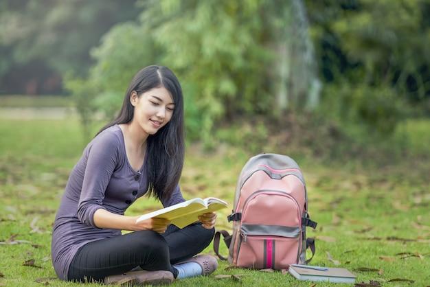 Портрет счастливой очаровательной азиатской женщины, читающей книгу на открытом воздухе
