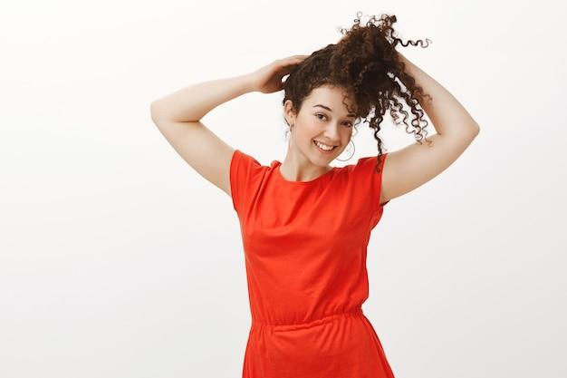 Портрет счастливой очаровательной кавказской женщины в модном красном платье, держащей вьющиеся волосы и расчесывающей их обеими руками