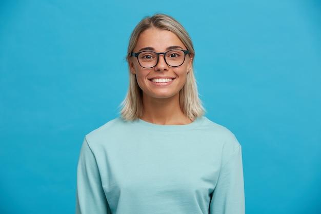 Портрет счастливой очаровательной веселой блондинки молодой женщины в очках, улыбается