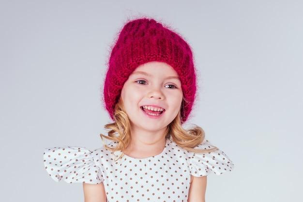 スタジオで白い背景にニットの赤い帽子とかわいい白いドレスを着て幸せな魅力的な少女の肖像画。ファッション秋冬シーズンセールコンセプト。願い事クリスマスの夜と誕生日を作る