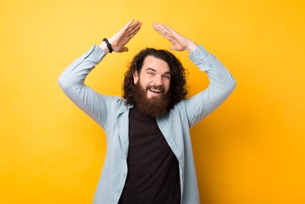 黄色の背景、セキュリティの概念の上に屋根のジェスチャーを作る幸せな魅力的な若い流行に敏感な男の肖像画