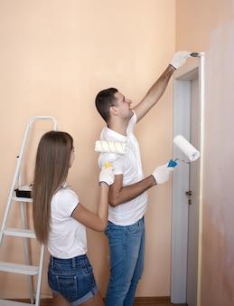 Портрет счастливой веселой пары, расписывающей интерьерную стену нового дома или квартиры