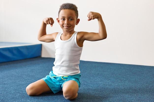 Портрет счастливого веселого темнокожего мальчика с короткой афро-прической, тренирующегося в фитнес-центре