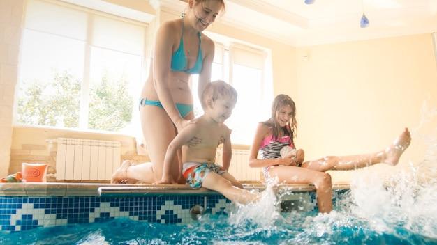 プールサイドに座って、足で水をはねかける幸せな陽気な家族の肖像画。家族で遊んだり、プールで楽しんだりする