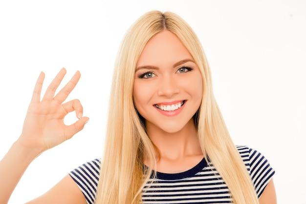 Okジェスチャーを示す幸せな陽気な女の子の肖像画