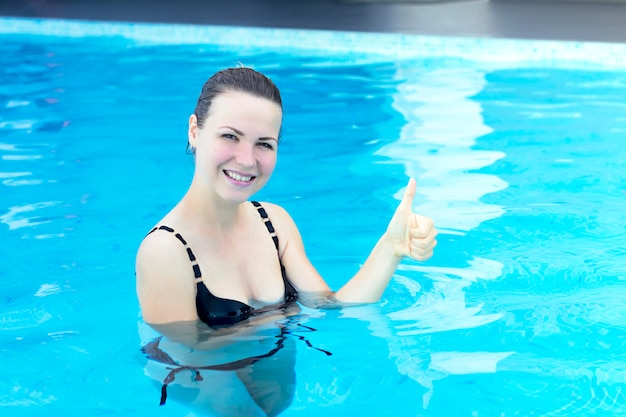 Портрет счастливой жизнерадостной девушки, пловца, положительной молодой женщины. дама стоит, наслаждайтесь в бассейне.